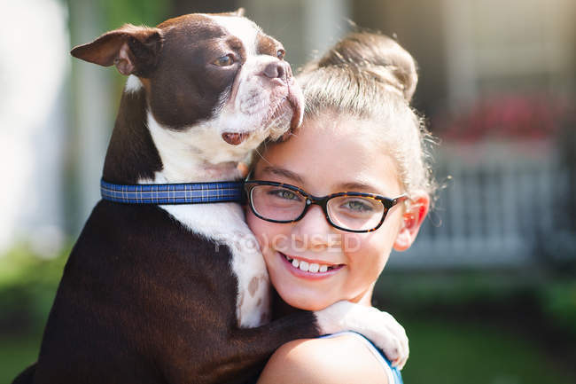 Portrait of girl carrying dog and smiling at camera — Stock Photo