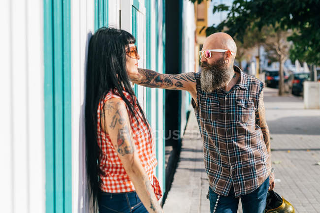 Mature hipster couple face to face on sidewalk — Stock Photo