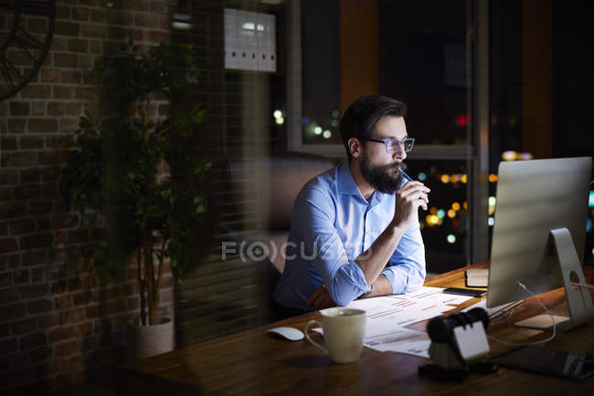 Young businessman looking at computer on office desk at night — Stock Photo