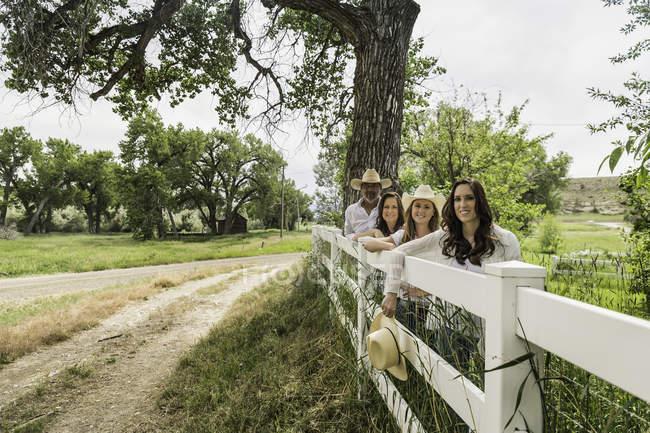 Ritratto di coppia adulta e le figlie che si appoggia contro recinzione ranch, Bridger, Montana, Stati Uniti — Foto stock