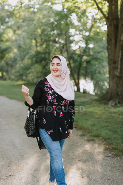 Young woman wearing in hijab walking on park — Stock Photo