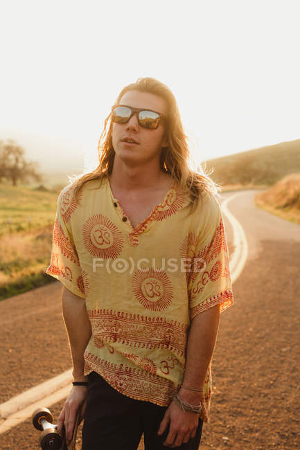 Portrait of long haired young male skateboarder on rural road, Exeter, California, USA — Stock Photo