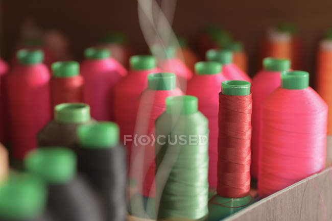 Red and green coloured threads in factory — Stock Photo