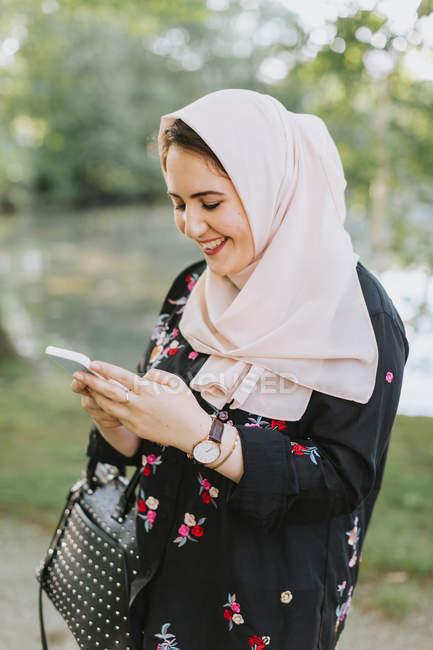 Mujer joven usando en hijab mirando el teléfono inteligente - foto de stock