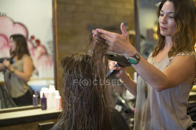 Femme coiffeuse travaillant avec le client dans le salon — Photo de stock