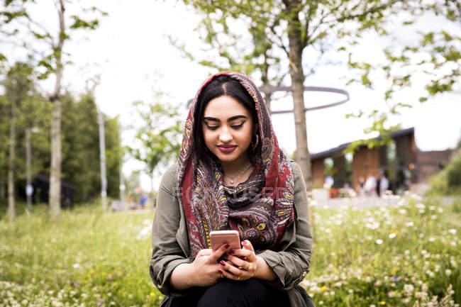 Vista frontal de la mujer usando hijab usando teléfono inteligente - foto de stock