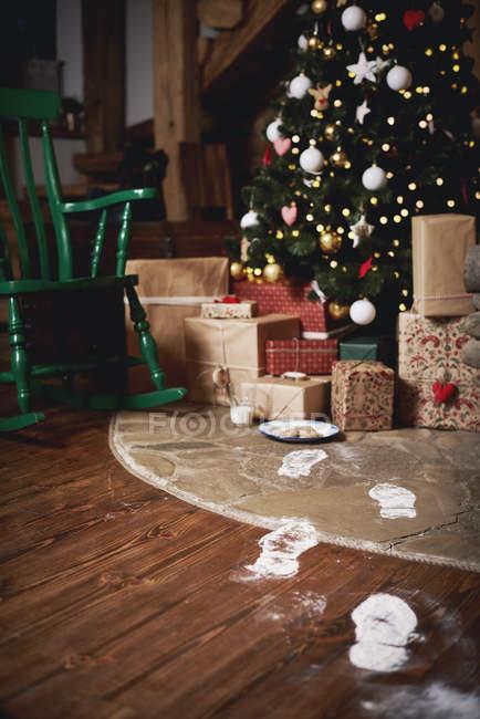 Árbol de Navidad rodeado de regalos, huellas de Santa conduciendo hacia el árbol - foto de stock