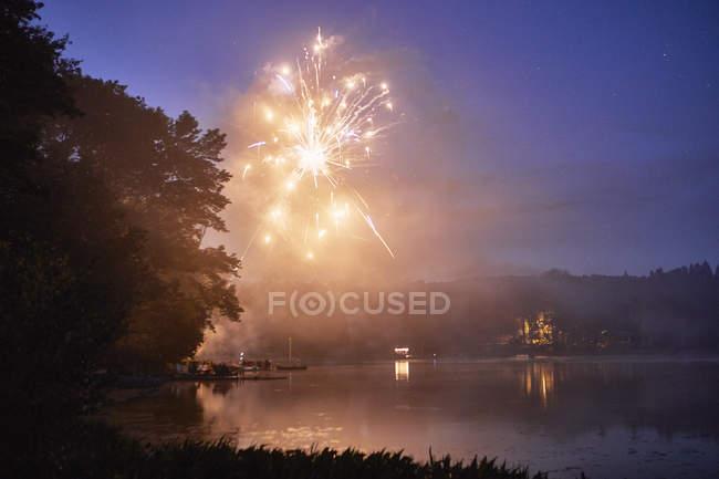 Fuegos artificiales explotan sobre el lago al atardecer - foto de stock
