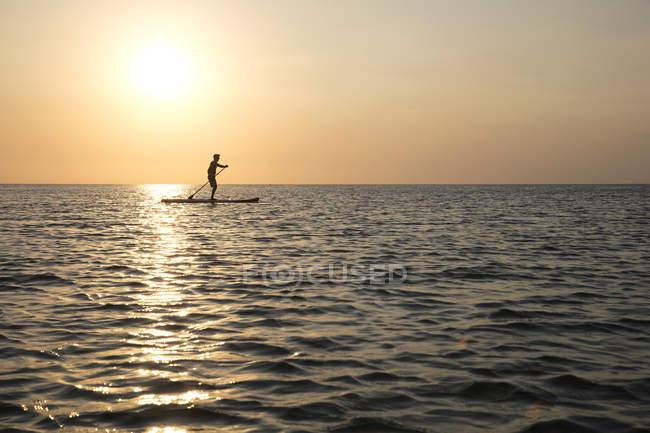 Vista lateral do homem em pé no paddleboard por do sol — Fotografia de Stock
