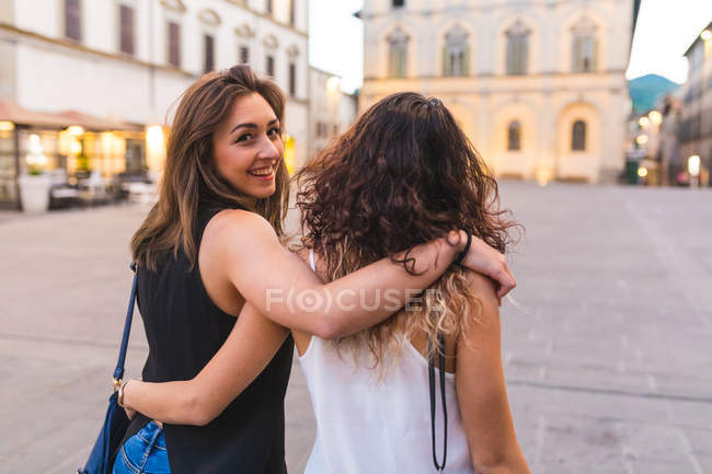 Young woman with arm around friend in city, looking over shoulder at camera smiling — Stock Photo