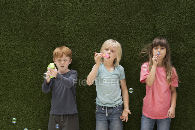 Children in front of artificial grass wall blowing bubbles — Stock Photo
