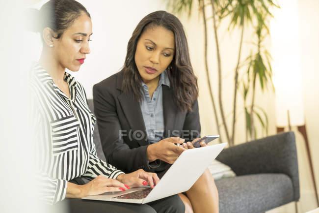 Dos mujeres de negocios con ordenador portátil y smartphone - foto de stock