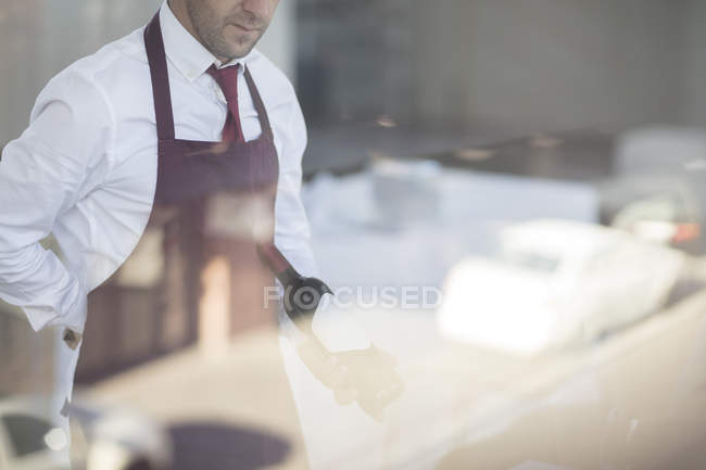 Waiter in restaurant holding bottle of wine, seen through window — Stock Photo