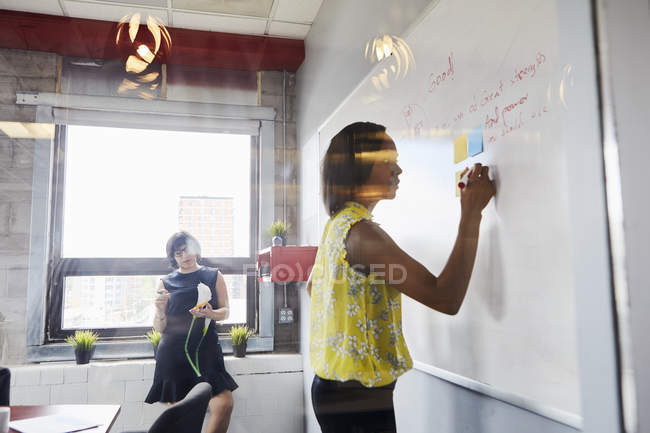 Two women in office using whiteboard and sticky notes — Stock Photo