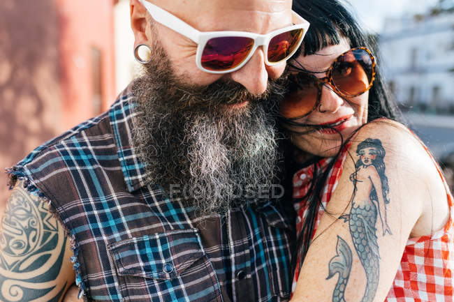 Mature tattooed hipster couple embracing on sidewalk, close up — Stock Photo