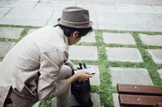 Junger Mann hält Smartphone und Tasche durchsuchen — Stockfoto