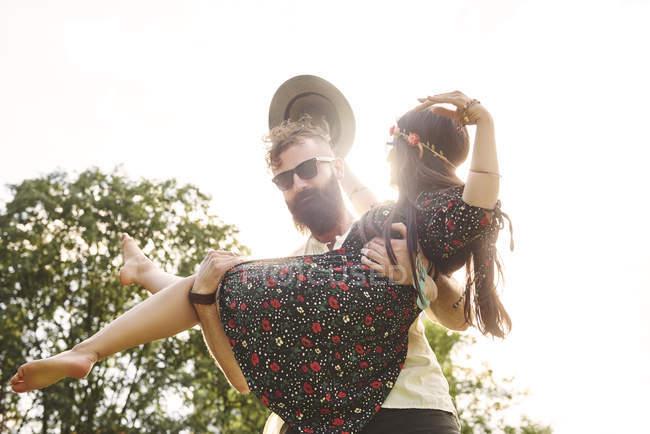 Jovem carregando boho namorada nos braços no festival ao ar livre — Fotografia de Stock