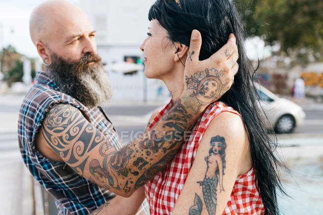 Mature tattooed hipster man with hand in girlfriend's hair — Stock Photo