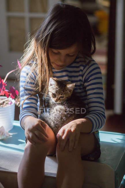Kätzchen im Sonnenaufgang sitzt auf dem Schoß eines Mädchens — Stockfoto