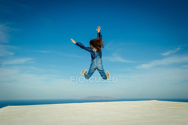 Vista trasera de la niña saltando en el aire con el mar en el fondo, Santorini, Kikladhes, Grecia - foto de stock