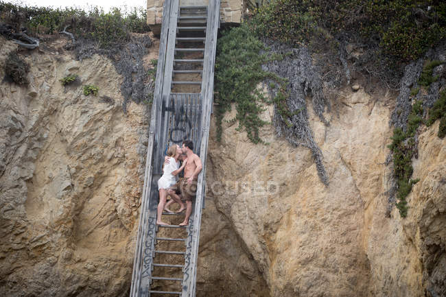 Romantic couple on stairs to beach, Malibu, California, US — Stock Photo
