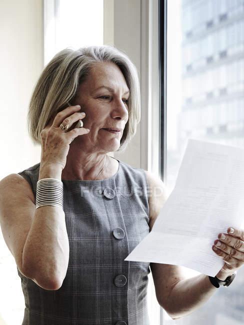 Старшого бізнес-леді за допомогою смартфона, читання документа — стокове фото