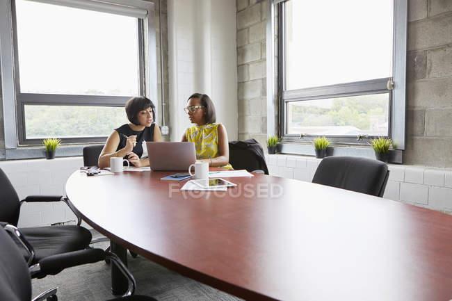 Deux femmes assis à la table de la salle de réunion et à l'aide d'ordinateur portable — Photo de stock