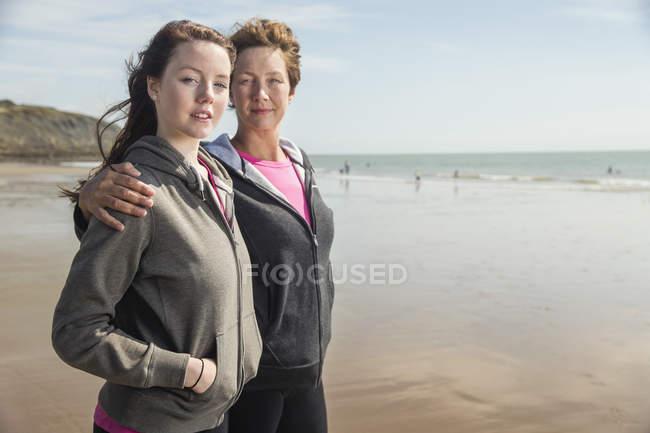 Mãe e filha olhando para a câmera na praia — Fotografia de Stock