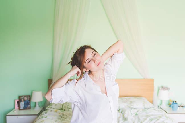 Giovane donna sul letto sbadiglio e stretching — Foto stock