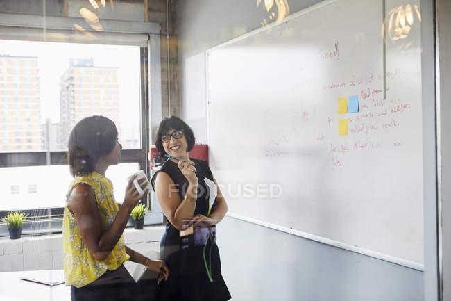 Two women in office using whiteboard — Stock Photo