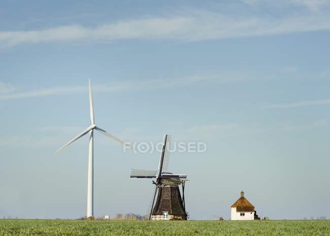 Современная ветряная турбина и традиционная голландская ветряная мельница стоят вместе, Workum, Фрисландия, Нидерланды — стоковое фото