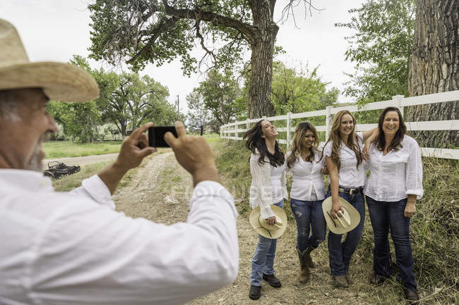 Mature man in cowboy hat photographing wife and young women on ranch, Bridger, Montana, USA — Stock Photo