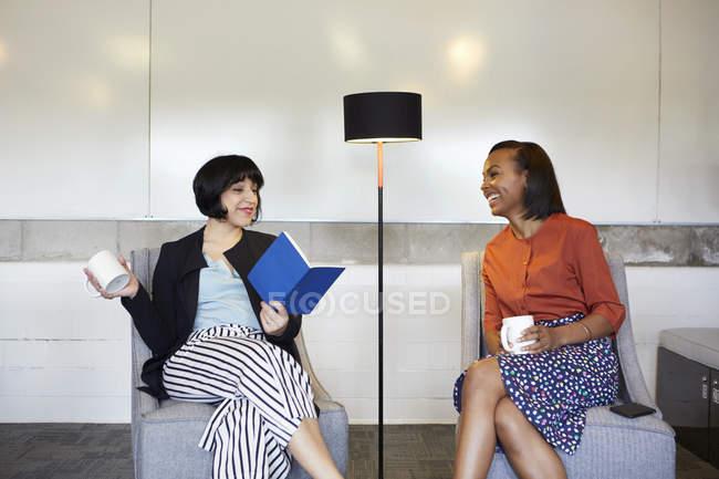 Две деловые женщины сидят в удобных креслах в офисе — стоковое фото