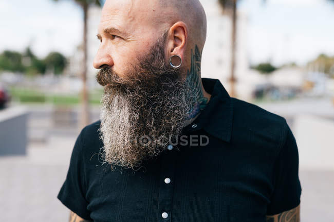 Portrait of mature male hipster with grey beard and earring plug, head and shoulders — Stock Photo