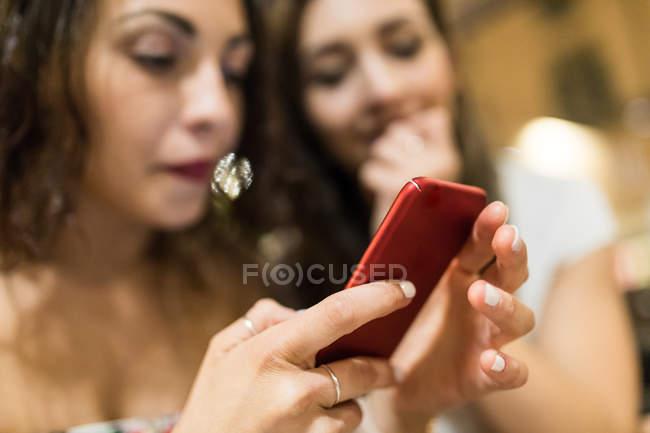 Mujeres jóvenes mirando juntos los teléfonos inteligentes - foto de stock