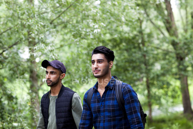 Two male friends walking in park together — Stock Photo