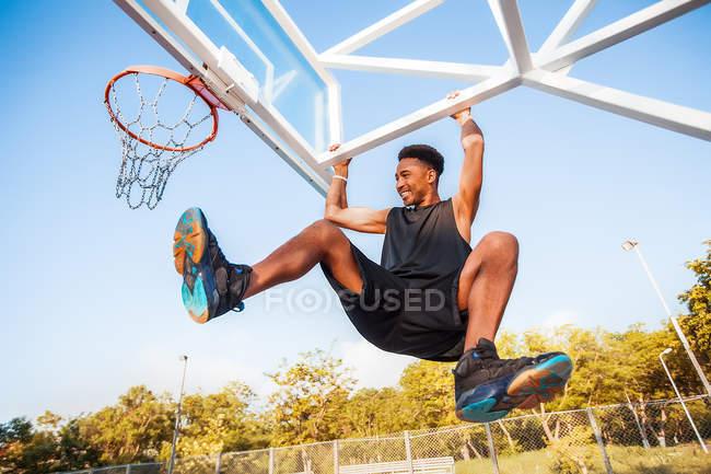 Молодой человек на баскетбольной площадке качается на баскетбольной сетке — стоковое фото