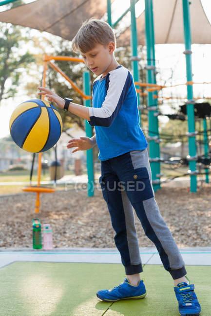 Junge hüpft Basketball auf Spielplatz — Stockfoto