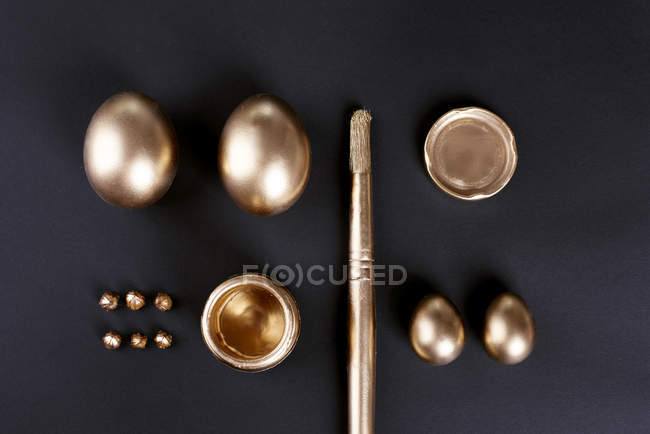 Top view of gold painted easter eggs and paintbrush on black background — Stock Photo