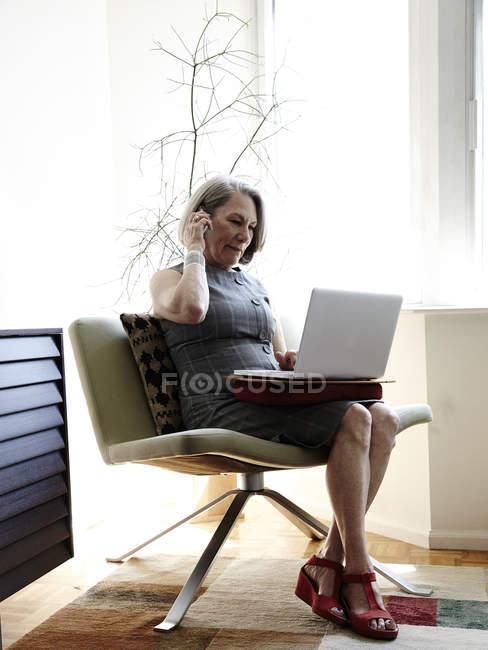 Старшого бізнес-леді сидить у кріслі, використовуючи ноутбук — стокове фото