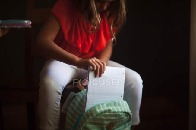 Vista cortada da mochila de embalagem da menina com suprimentos de papelaria — Fotografia de Stock