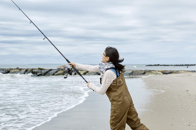 Young woman casting fishing rod from beach — Stock Photo
