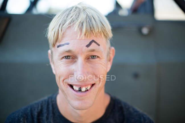Retrato de jovem com cabelo mal cortado, desenhado em sobrancelhas e dentes apagados — Fotografia de Stock