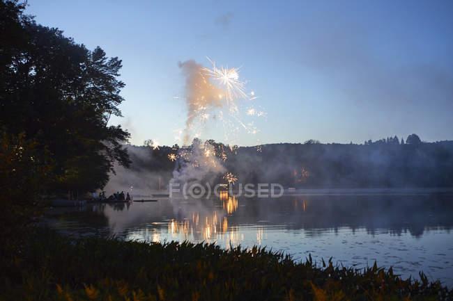 Fuegos artificiales explotan sobre el lago - foto de stock