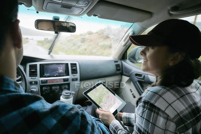 Пара в машине и женщина держит цифровой планшет с картой — стоковое фото