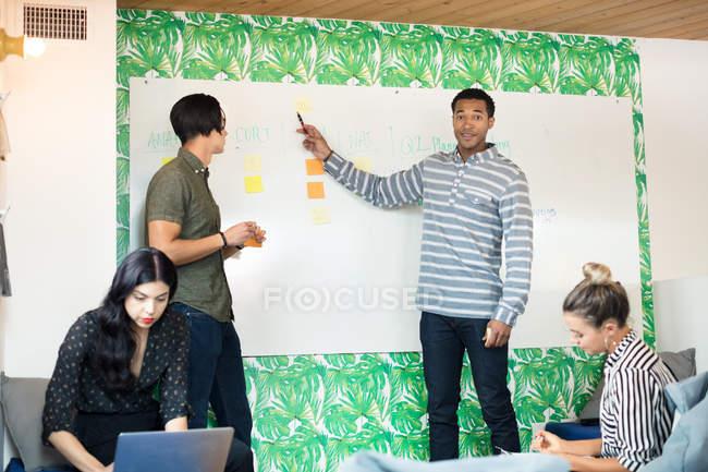Collègues de travail avec tableau blanc bureau créatif — Photo de stock