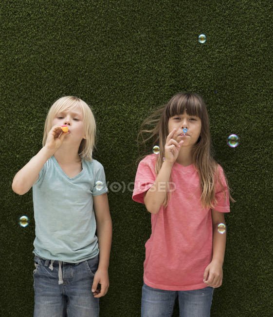 Two kids in front of artificial grass wall blowing bubbles — Stock Photo
