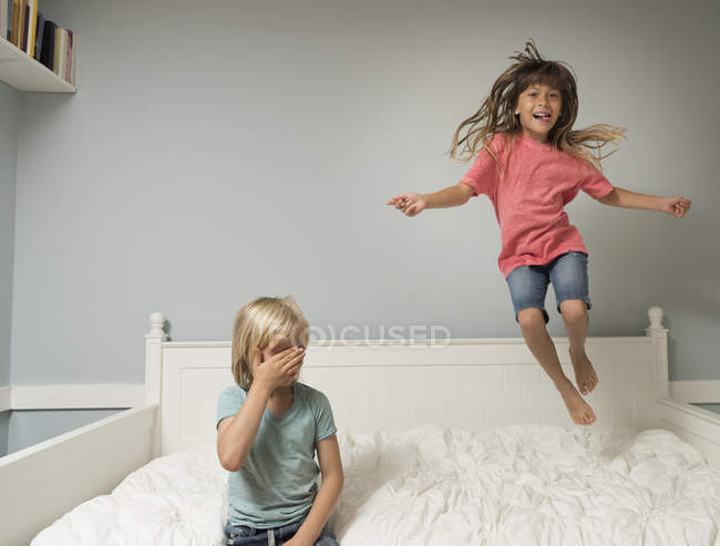 Girl in mid air jumping on bed in bedroom — Stock Photo