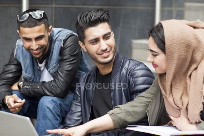 Trois amis assis sur les marches avec ordinateur portable — Photo de stock