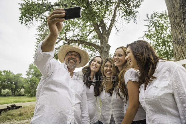 Mature couple prenant selfie smartphone avec des jeunes femmes sur ranch, Bridger, Montana, Usa — Photo de stock